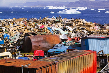 Rubbish dumped on the tundra outside Illulissat, Greenland with icebergs behind from the Sermeq Kujullaq or Illulissat Ice fjord, UNESCO World Heritage Site, Greenland. July 2008