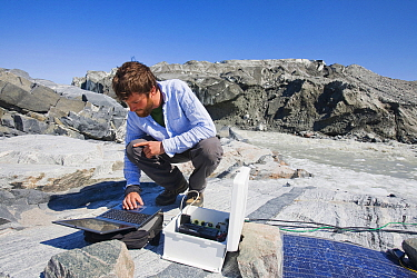 Scientist taking readings from the meltwater river at the snout of the Russell Glacier near Kangerlussuaq, Greenland. July 2008