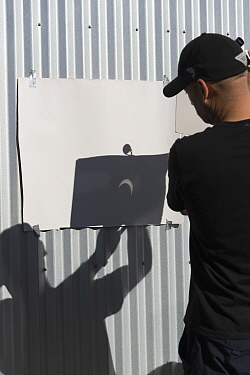 Man projecting annular solar eclipse, onto white sheet with binoculars, Aisen Region, Patagonia, Chile, February 2017.