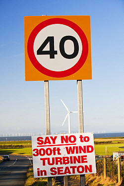 Protest sign about a new wind turbine in Seaton near Workington, Cumbria, England, UK. With onshore wind turbines and the offshore Robin Rigg wind farm visible. January 2012