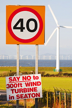 Protest sign about a new wind turbine in Seaton near Workington, Cumbria, UK, with onshore wind turbines and the offshore Robin Rigg wind farm visible. January 2012