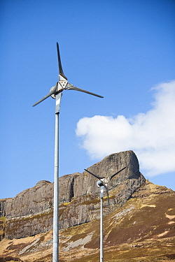 Wind turbines beneath An Sgurr, Isle of Eigg. Isle of Eigg produces all the energy the island nees from renewable energy. Eigg, Scotland, UK, May.
