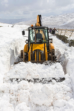 JCB clearing a way through massive snow drifts blocking the Kirkstone Pass road above Ambleside,Lake District, UK. March 2013