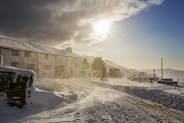 The Kirkstone Pass Inn, plastered in fresh snow after overnight snow storms and with spindrift from drifting snow in windy conditions in the Lake District, Cumbria, UK. January 2016