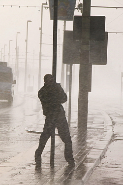 Man holding onto post during severe storm with hurricane force winds, Blackpool, England, UK, November 2007.
