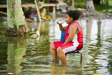 Child sitting on chair in floodwaters on Funafuti,Tuvalu. These low lying islands are very susceptible to sea level rise, March 2007