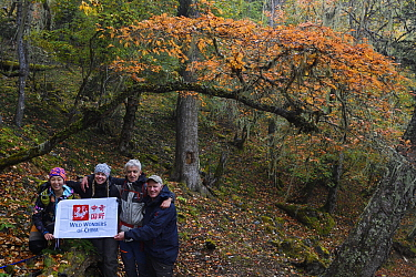 Wild Wonders of China. team holding up their flag in the lichen-covered (Usnea longissima) temperate cloud forest, in the Meili Snow Mountain National park, Yunnan China. October