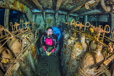 Diver swimming through wreck, compressor room of USS Kittiwake, US Military submarine rescue vessel. Seven Mile Beach, Grand Cayman, Cayman Islands, British West Indies. Caribbean Sea. January, 2018.