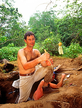 Cameraman Michael Pitts with newly hatched Komodo dragon (Varanus komodensis) at megapode mound where the female  laid her eggs. Komodo Island, Indonesia. 1995