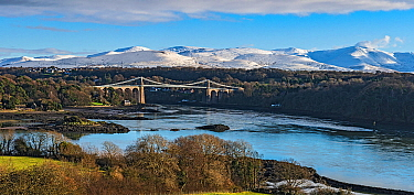 Menai Suspension Bridge, designed by Thomas Telford, viewed from Anglesey across Menai Strait, with snow capped hills in background. North Wales, UK. December 2017