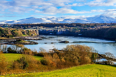 Menai Suspension Bridge, designed by Thomas Telford, viewed from Anglesey across Menai Strait, with snow capped hills in background. North Wales, UK. December 2017.