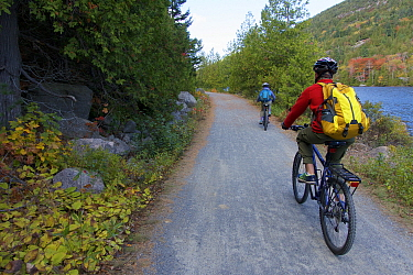 Cycling on a carriage road along a lake in Acadia National Park, Maine, USA. October 2013. Model released.