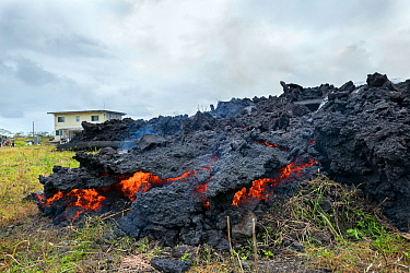 A'a lava flowing over land, where it has pushed down a house and set it on fire. The lava originated from Pu'u O'o, Kilauea Volcano, from a fissure in Leilani Estates, near Pahoa, Puna, Hawaii, USA....