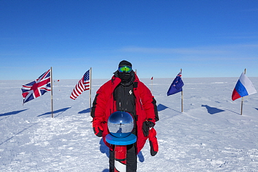 Wildlife photographer Sue Flood at ceremonial South Pole 90 degrees South near Scott-Amundsen, Antarctica. December 2016