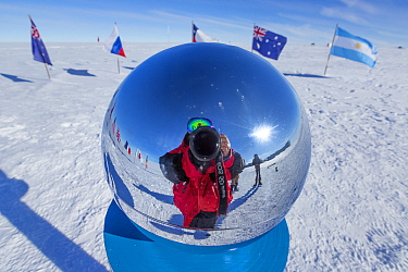 Wildlife photographer Sue Flood reflected in marker at ceremonial South Pole 90 degrees South near Scott-Amundsen base, Antarctica. December 2016