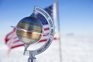 Marker to show geographical South Pole 90 degrees South with USA flag, near Scott-Amundsen base, Antarctica.December 2016