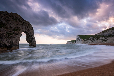 Durdle Door, with incoming tide at sunset, near Lulworth, Dorset Jurassic coast, UK. June 2017.