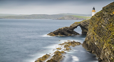 Sea arch and lighthouse, Bressay with Lerwick in background, Shetland Islands, Scotland, UK. July, 2014.