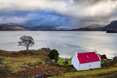 Red roofed croft overlooking Loch Sheildaig, Loch Torridon, Applecross Peninsula, Highlands, Scotland, UK. January 2015.