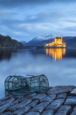 Lobster pots at edge of Loch Duich, Eilean Donan Castle in background. Highlands, Scotland, UK. January 2014.