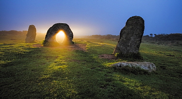 Sunrise through stone at Men-An-Tol, Morvah, Cornwall, England, UK. September 2016.