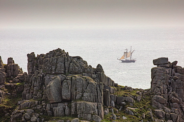 Schooner passing Logan Rock, Treen, Cornwall, England, UK. September 2017.