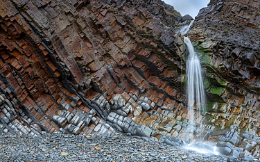 A small waterfall at Sandy Mouth beach, near Bude, Cornwall, UK, March. The rocks are steeply dipping Carboniferous age, sandstone and shale (Culm Measures).