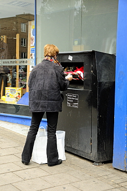 Woman recycling clothes into a clothes bank outside charity shop, Highbury Corner, London Borough of Islington, UK