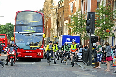 Commuter cyclists and bus in rush hour traffic, Angel, London Borough of Islington, England, UK, May 2009