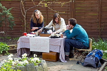Three people sitting around a vintage sewing machine on a table outdoors. A label on the front says 'DIY Mending and Styling!' Hackney City Farm, London, England UK, March 2011