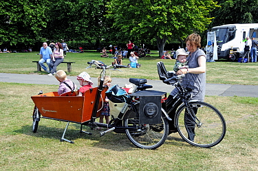 Woman with with bicycle and four small children, two in a workcycles trailer. London Green Fair (previously Camden Green Fair) England, UK, June 2011