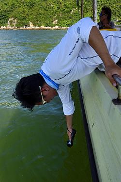 Scientist measuring water data whilst monitoring Indo-Pacific humpback dolphin (Sousa chinensis) Tai O, Lantau Island, Hong Kong, China. June, 2016.