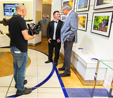 Photographers Oliver Hellowell and Ken Jenkins (Tennessee based photographer) being filmed at their joint exhibition at the T5 Gallery, Heathrow Airport, England, UK. July.