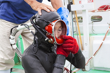 Ama diver adjusting her mask and breathing hose before going into the ocean to work. Futo Harbour, Izu Peninsula, Shizuoka Prefecture, Japan. June 2010.