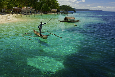 View of beach, and man fishing from a dugout canoe, at Yenbeser Village. Alfred Russel Wallace based himself in this village for several months in the 1850's. Raja Ampat Islands, Indonesia. May 2007