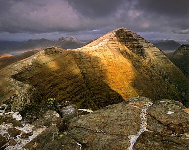 Break in the thunderclouds illuminating the summit of Beinn Alligin, Tom na Gruigach, Torridon mountains, Highlands, Scotland.