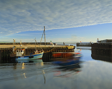 Slow exposure of a fishing boat leaving Burghead Harbour on a summer evening in Moray, Scotland.
