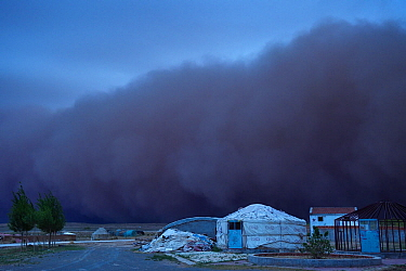 Sand storm rolling in over lodges on farm, Inner Mongolia, China