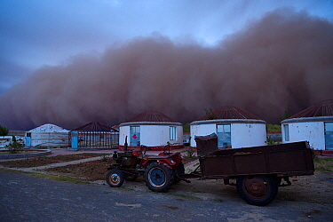 Sand storm rolling in towards lodges on farm, Inner Mongolia, China
