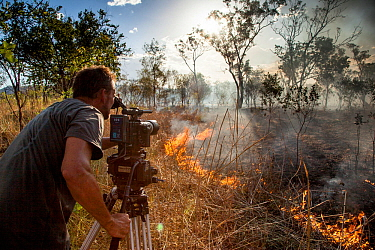 Cameraman Murray Fredericks films a wildfire triggered by lightning for Storm Chasing programme in Northern Australia for BBC Wonders of The Monsoon. Western Australia. December 2013.