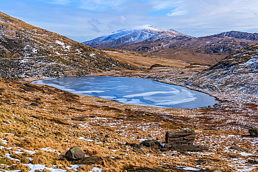 Frozen Llyn Teyrn with Moel Siabod, Conwy in background, view east from Miner's Track. Snowdonia National Park, Gwynedd, Wales, UK. March 2018.