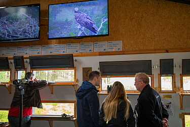 Visitors at Loch Garten Osprey Centre with live Osprey (Pandion haliaetus) footage on screens. Boat of Garten, Cairngorms National Park, Scotland, UK.