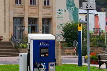 Electric car charging point in front of Saxon Switzerland National Park information centre. Eurasian lynx (Lynx lynx) branding on wall. Bad Schandau, Saxony, Germany.