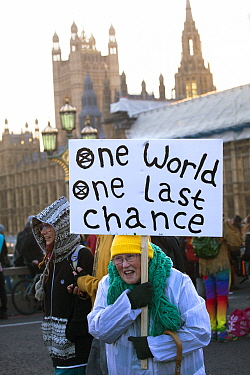 Woman holding 'One World One Last Chance' placard during Extinction Rebellion demonstration to draw attention to climate change. Five bridges across the Thames were blocked. Houses of Parliame...