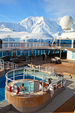 Cruise ship passenger in outdoor hot tub, near mountains, Paradise Bay, Antarctica, January.