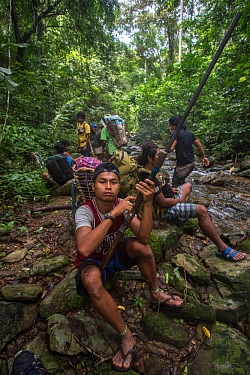 Young Batak man holding a home-made hunting rifle on an almaciga tree (Agathis philippinensis) cone collecting expedition in Cleopatra's Needle Critical Habitat, Palawan, the Philippines. Septembe...