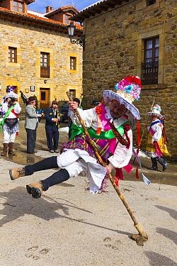 Man leaping over stick in traiditional costume, Carnival of Zamarrones, Pejanda village, Polaciones valley, Cantabria, Spain. February 2013.