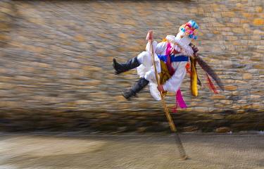 Man leaping over stick in traiditional costume, Carnival of Zamarrones, Pejanda village, Polaciones valley, Cantabria, Spain.