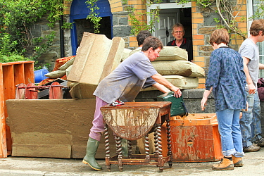 People trying to clear water after flooding, surrounded by flood damaged furniture, Ceredigion, Wales, UK, June 10th 2012