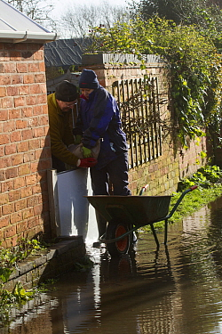 Couple installing sand bags to prevent flooding to their home during February 2014 floods, Upton Upon Severn, Worcestershire, England, UK, 8th February 2014.